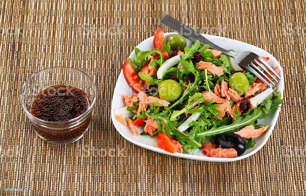 Fresh healthy salad and dressing on natural bamboo place mat stock photo