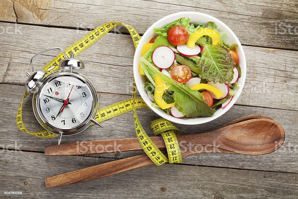 Fresh healthy salad and measuring tape on wooden table stock photo