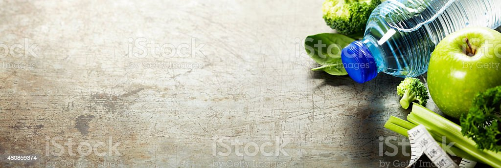 Fresh healthy vegetables, water and measuring tape. stock photo