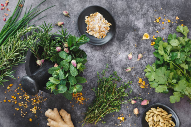 Fresh herbs and spices being ground up in mortar and pestle Fresh herbs and spices being ground up in mortar and pestle on dark background. Top view, blank space thyme photos stock pictures, royalty-free photos & images