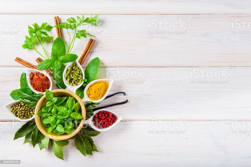 Fresh herbs and spices on a white wooden background stock photo