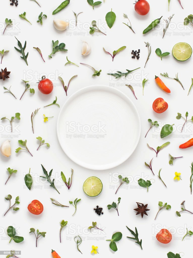 Fresh herbs and vegetables and plate on white background. stock photo