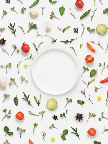 frische kräuter und gemüse und platte auf weißem hintergrund. - kräuterdiät stock-fotos und bilder