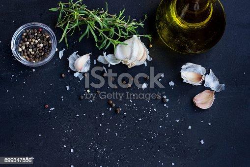 Fresh Herbs, Garlic, Pepper and Oil Olive on Black Background