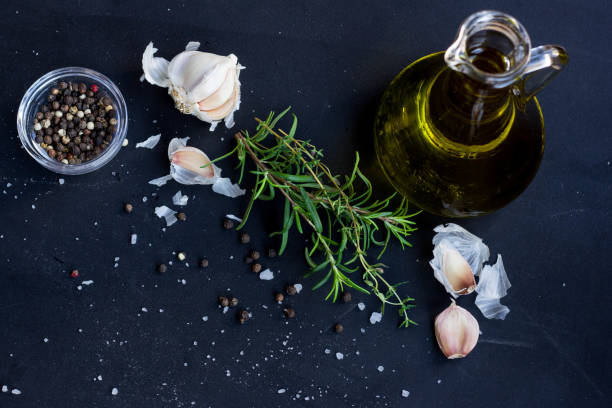 Fresh Herbs, Garlic, Pepper and Olive Oil  on Black Background stock photo
