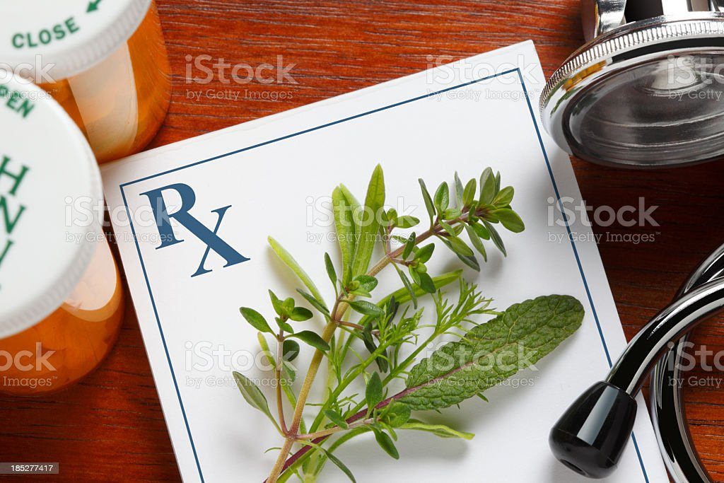 Fresh herbs on top of a doctor's prescription pad stock photo