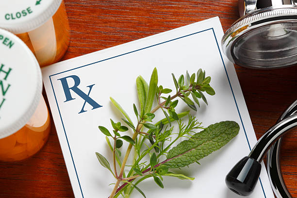 fresh herbs on top of a doctor's prescription pad - naturopathy stock photos and pictures