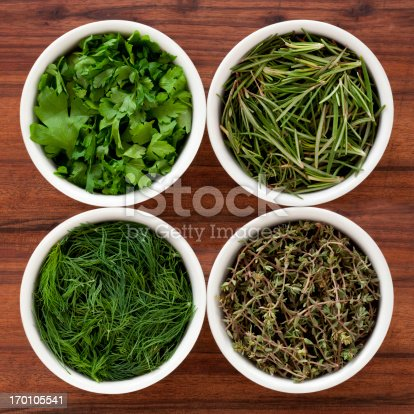 Four bowls containing varieties of fresh herbs (parsley, rosemary, dill and thyme)
