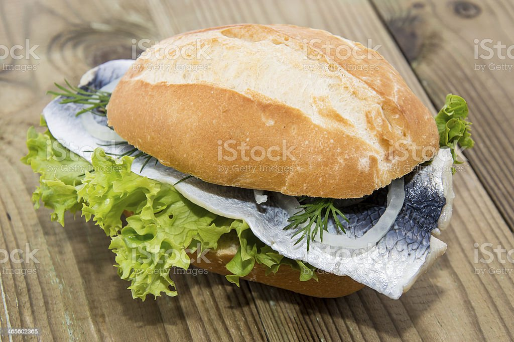 Fresh herring sandwich in a wooden table stock photo