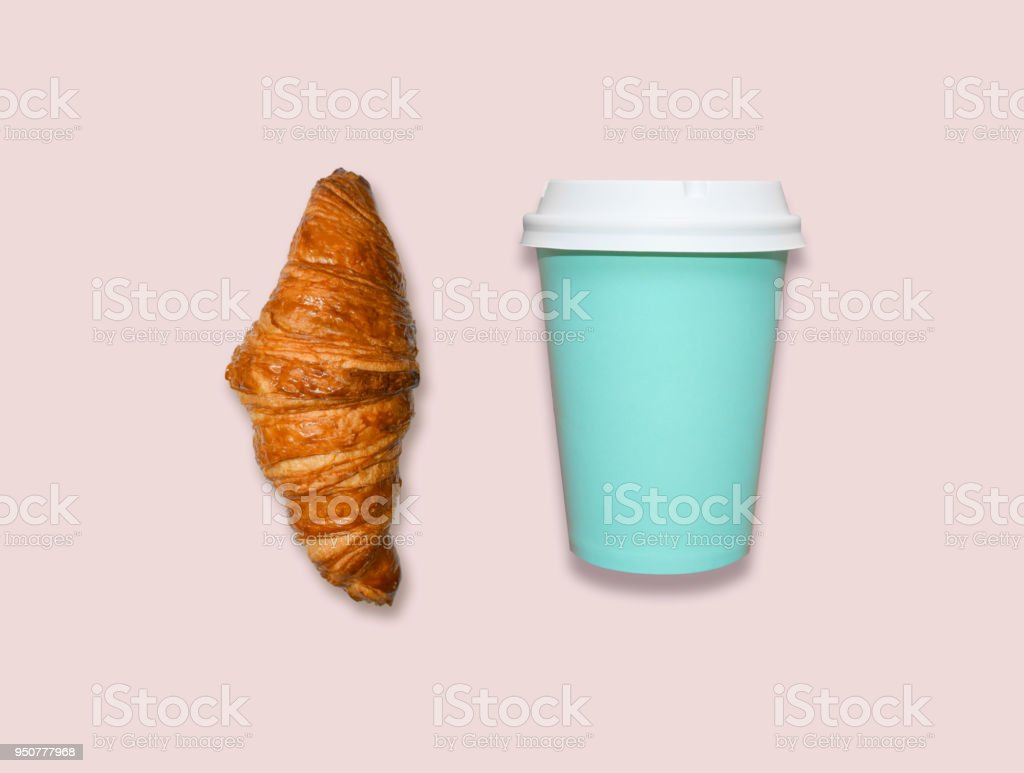 Fresh home made croissant and cappuccino take away cup on pink table, top view.