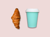 istock Fresh home made croissant and cappuccino take away cup on pink table, top view. 950777968