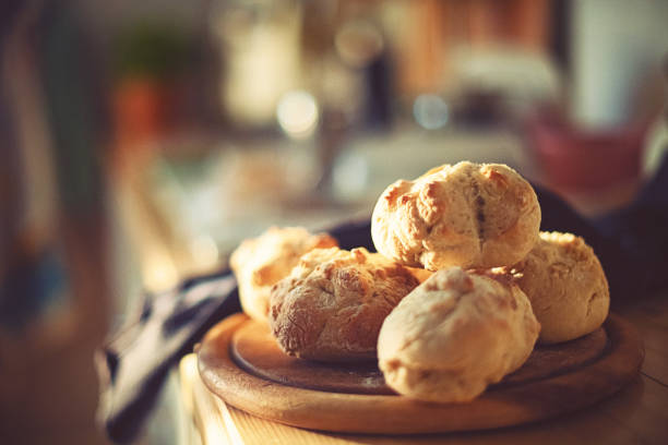 fresh home-baked wheat rolls are ready for breakfast in the morning light stock photo
