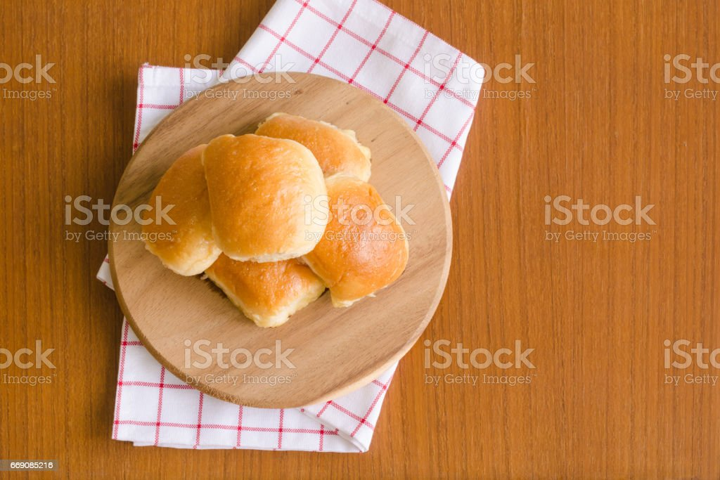 Fresh homemade baking delicious butter bun bread over wooden tray on red and white napkin on brown teakwood floor background with sunlight on the side for happy breakfast with copy space on the right stock photo