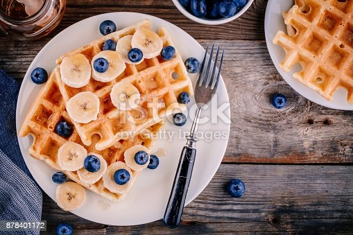 istock Fresh homemade belgian waffles with blueberries and banana for breakfast 878401172