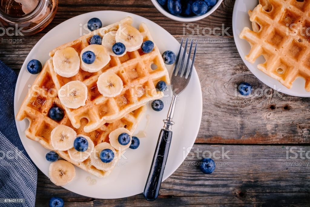 Fresh homemade belgian waffles with blueberries and banana for breakfast stock photo