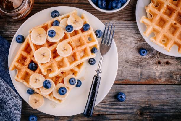 frische hausgemachte waffeln mit heidelbeeren und bananen zum frühstück - gebackene banane stock-fotos und bilder