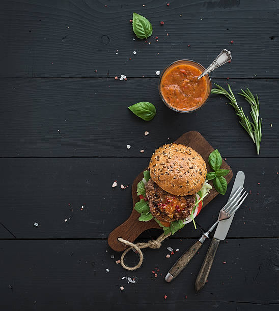 Fresh homemade burger on dark serving board with spicy tomato stock photo
