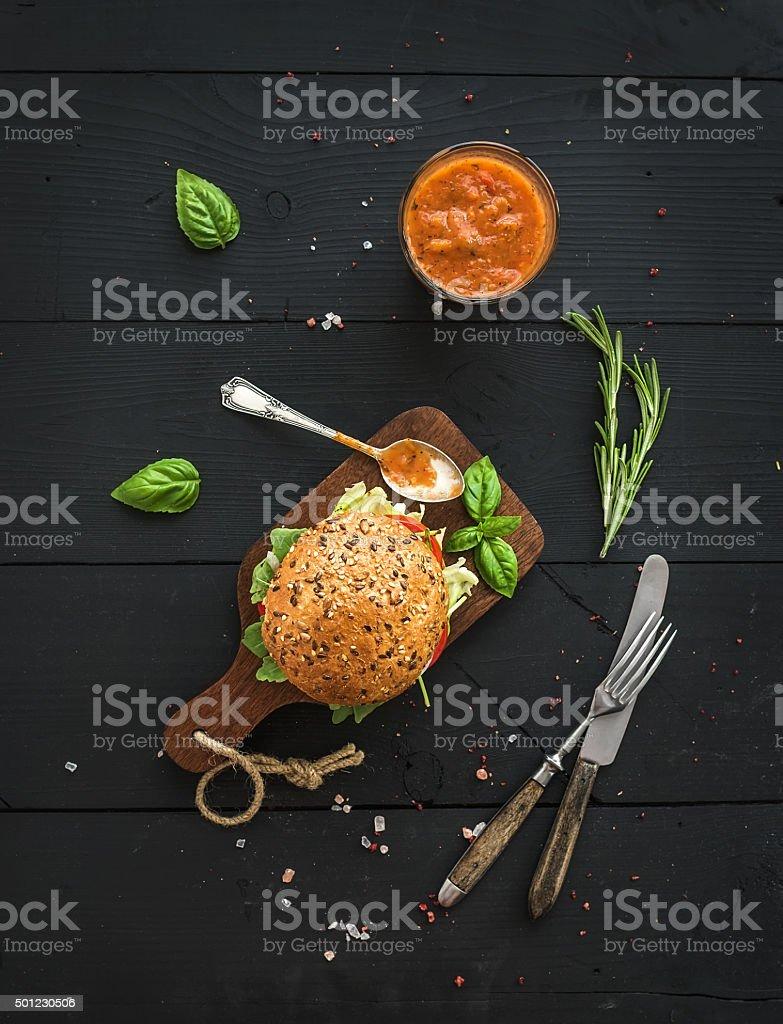 Hambúrguer caseiras frescas no escuro tábua com molho picante de tomate - foto de acervo