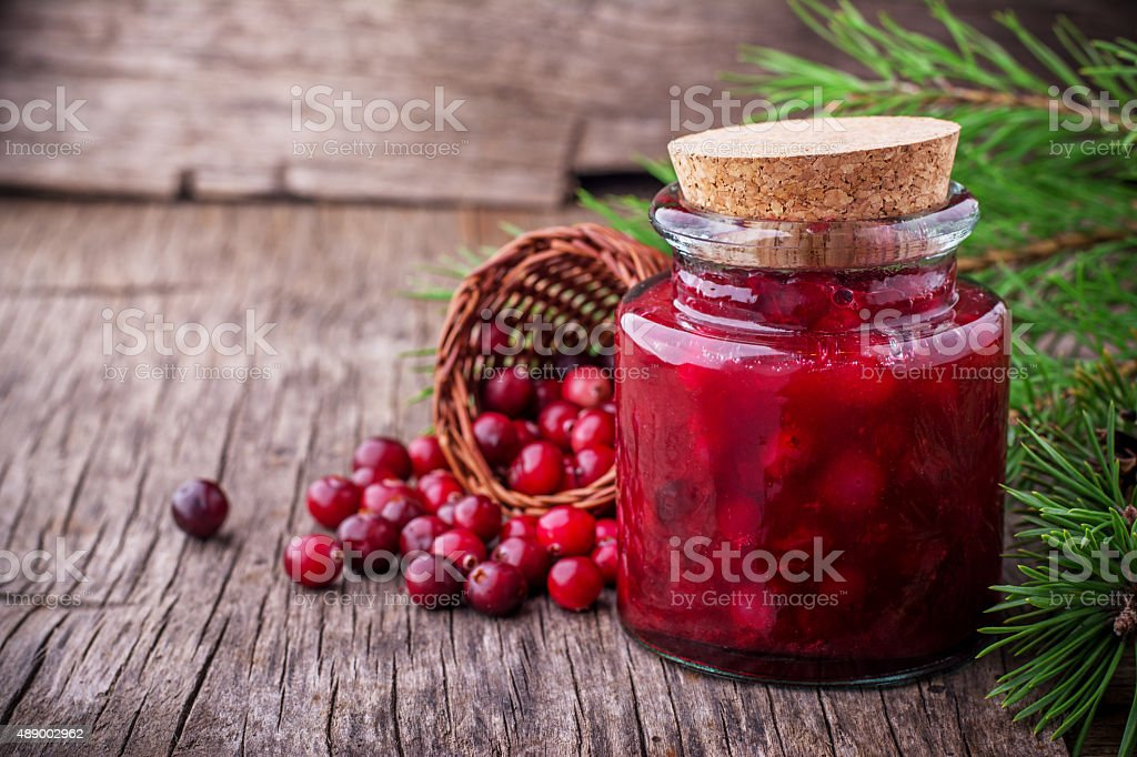 Fresh homemade cranberry sauce in a glass on dark wooden stock photo