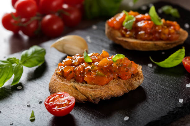 Fresh homemade crispy Italian antipasto called Bruschetta topped with different vegetables stock photo