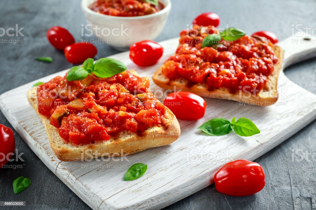 Fresh homemade crispy Italian appetizer Bruschetta topped with tomato, eggplant, Zucchini, Yellow pepper, garlic and basil on white wooden board. healthy food - foto stock