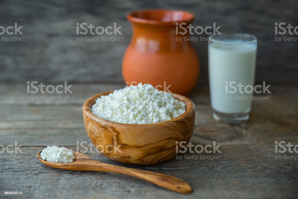 Fresh home-made curd in a wooden bowl on a linen napkin, with a glass of milk and a clay jug on a wooden old background. - Royalty-free Backgrounds Stock Photo