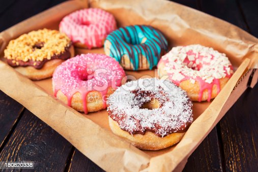 A box with fresh homemade donuts with icing.