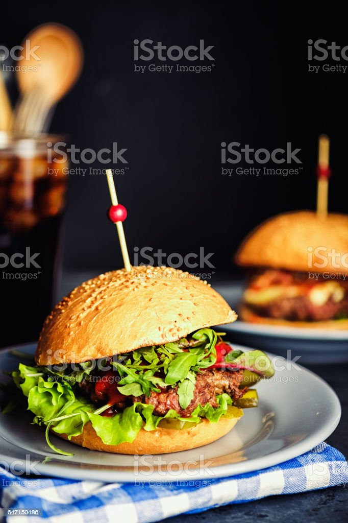Fresh homemade hamburger  in grey plate, over wooden table with dark background стоковое фото