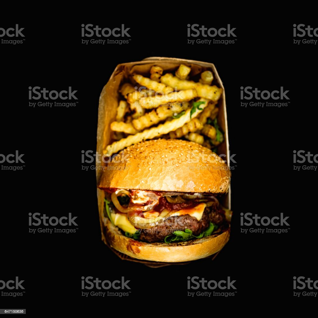 Fresh homemade hamburger with fried potatoes packed in a box on a black background. Top view. стоковое фото