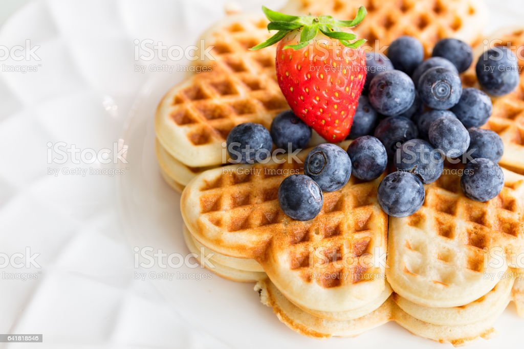 Fresh homemade heart shape waffles with blueberries and strawberry on white plate stock photo