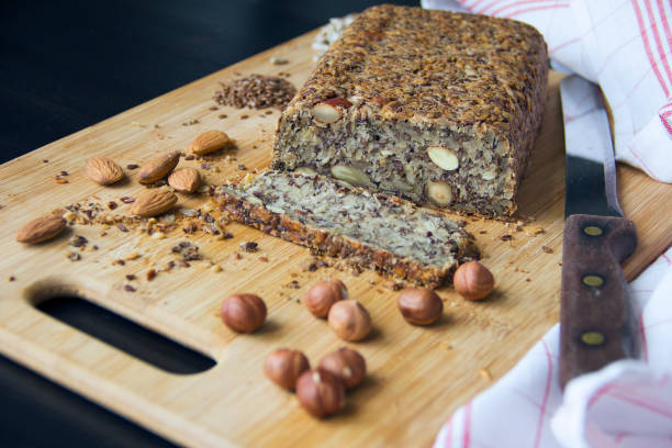Fresh homemade keto bread with almonds, hazelnuts, sunflower seeds, chia seeds Fresh homemade keto bread with almonds, hazelnuts, sunflower seeds, chia seeds on a wooden cutting board low carb diet stock pictures, royalty-free photos & images
