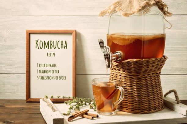 Frische hausgemachte Kombucha fermentierte Teegetränk in einem Glas mit Wasserhahn und in einer Tasse auf einem weißen Tablett, das Rezept für das Kochen im Rahmen, Holzhintergrund – Foto