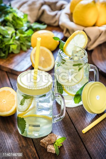 Two jars of fresh homemade lemonade with lime, brown sugar and mint leaves on rustic wooden table. At the background is a wooden cutting board with a bunch of mint on top and at right top corner is a bowl full of limes. Low key DSLR photo taken with Canon EOS 6D Mark II and Canon EF 24-105 mm f/4L