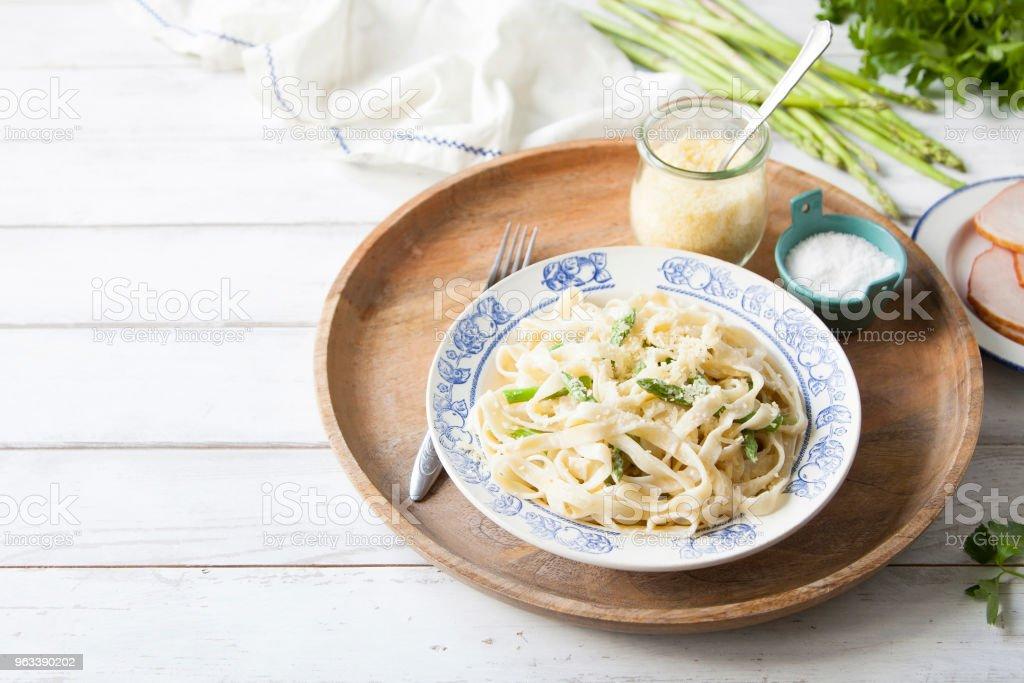 Fresh homemade pasta with asparagus, cheese and cream sauce on wooden tray. - Zbiór zdjęć royalty-free (Bez ludzi)