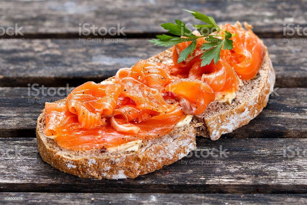 Fresh homemade sandwich with salmon on old wooden table stock photo