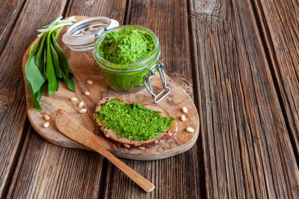 Pesto de alho selvagem caseiro fresco feito com ervas de alho-poró urso, delicioso molho salgado para massa italiana - foto de acervo