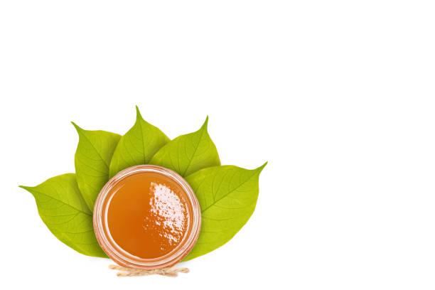 Verse honing in een glazen kom op de achtergrond van bladeren. Geïsoleerd op wit foto