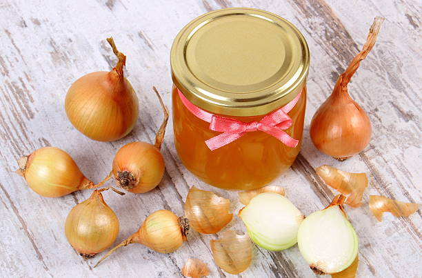 Fresh honey in glass jar and onions on wooden background stock photo