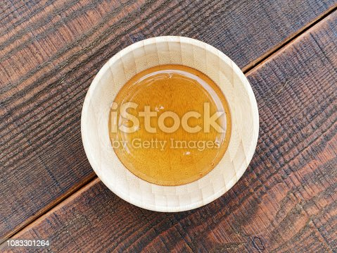 Fresh honey in wooden honey bowl on wooden table, top view.