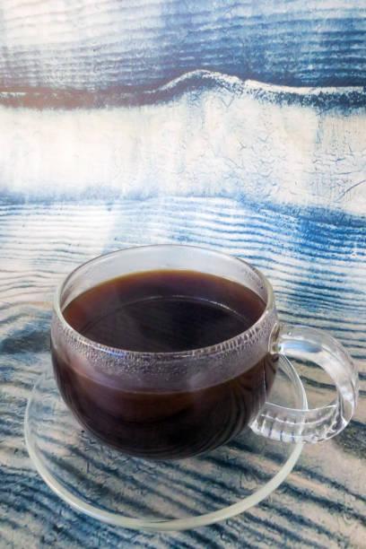 Frischer heißer schwarzer Kaffee in einer Glastasse auf blauem Holzhintergrund – Foto