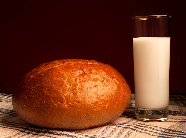 Fresh hot bread and cold milk Fresh hot bread and cold milk in a glass with glass, photographed in warm colors round loaf stock pictures, royalty-free photos & images