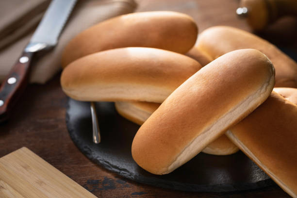 Fresh hot dog buns on a wooden surface Fresh hot dog buns on a wooden surface sweet bun stock pictures, royalty-free photos & images