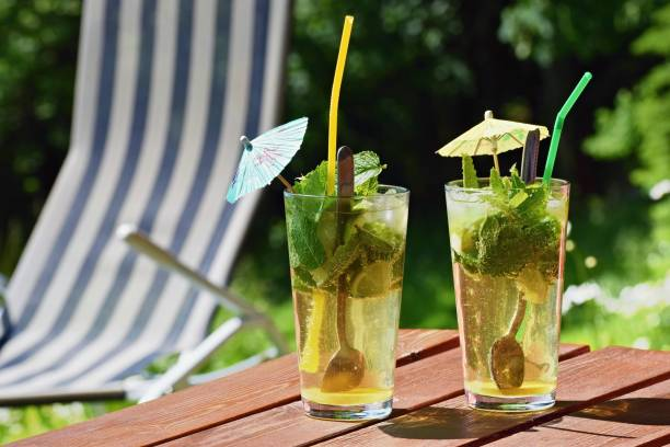 Fresh icy drink on the table with  summer garden on the background stock photo