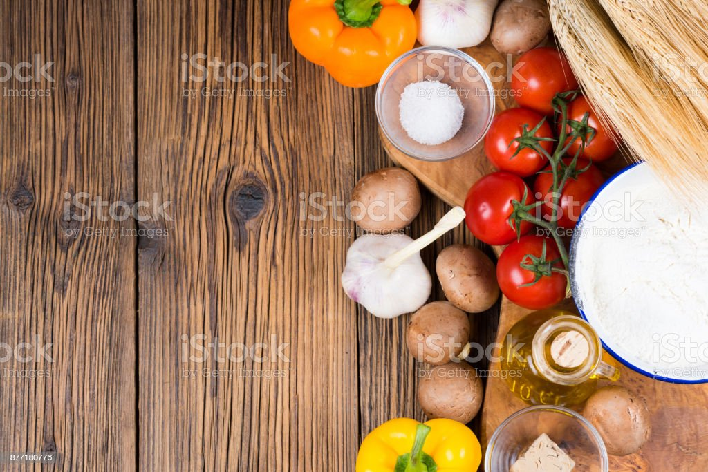 Fresh ingredients for a pizza dough and pizza topping on a wooden board made of olive wood with copy space in the left part of the picture stock photo
