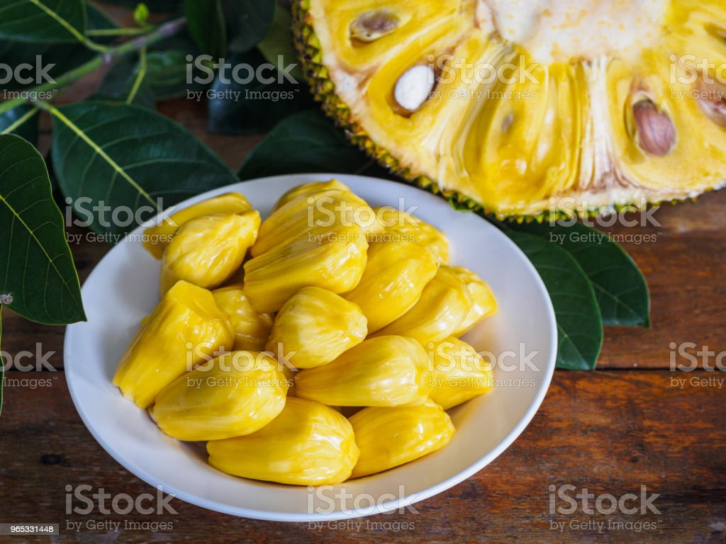 Fresh Jackfruit in white dish, half of jack fruit and jackfruit leaf on wooden table. royalty-free stock photo