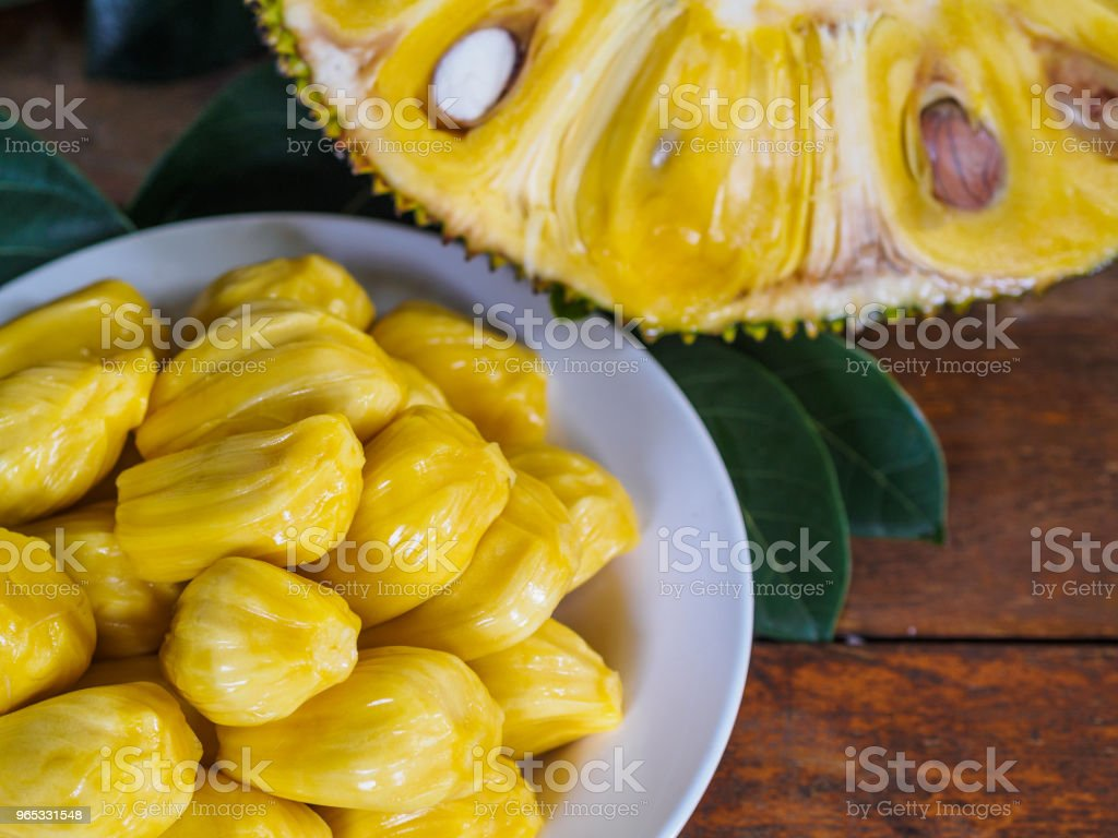 Fresh Jackfruit in white dish, half of jack fruit and jackfruit leaf on wooden table. royalty-free stock photo