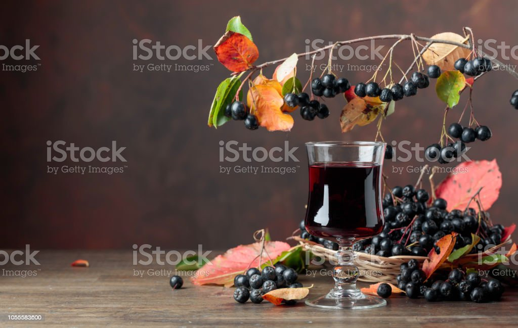 Fresh juice of ripe black chokeberry in glass and berries with leaves. – zdjęcie