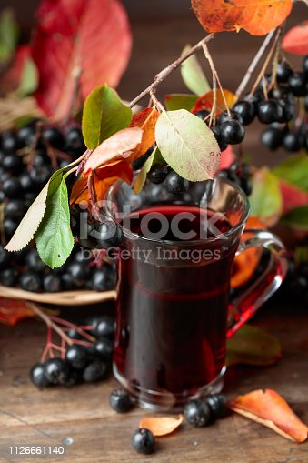 istock Fresh juice of ripe black chokeberry in glass and berries with leaves. 1126661140