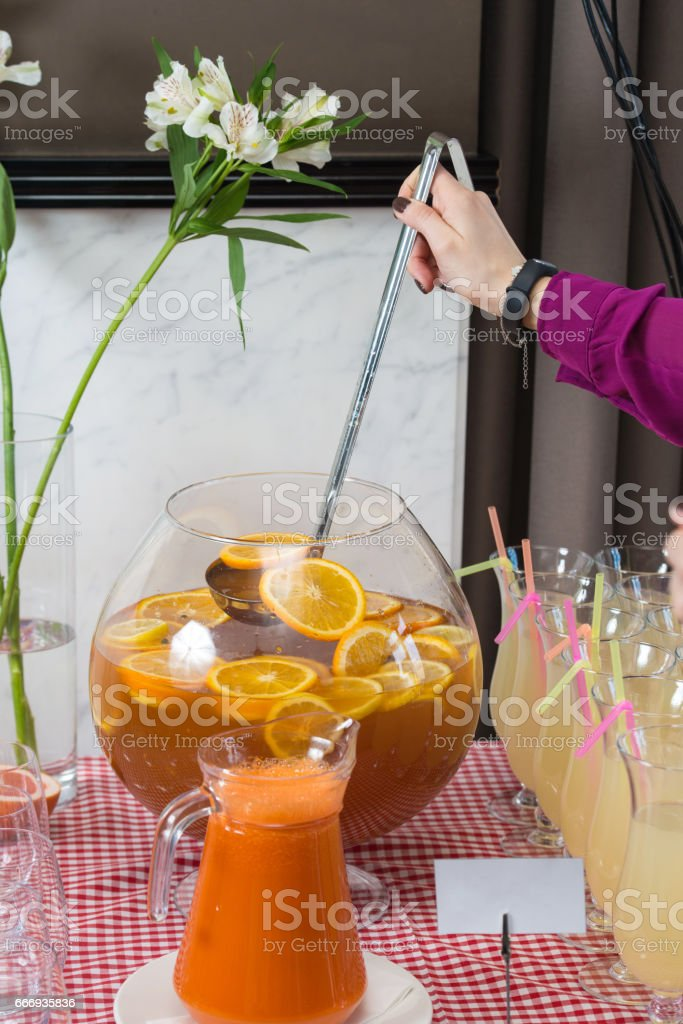 Fresh juice on a table in a restaurant. Healthy drinks. carrot fresh in a jar. Girl pouring juice stock photo