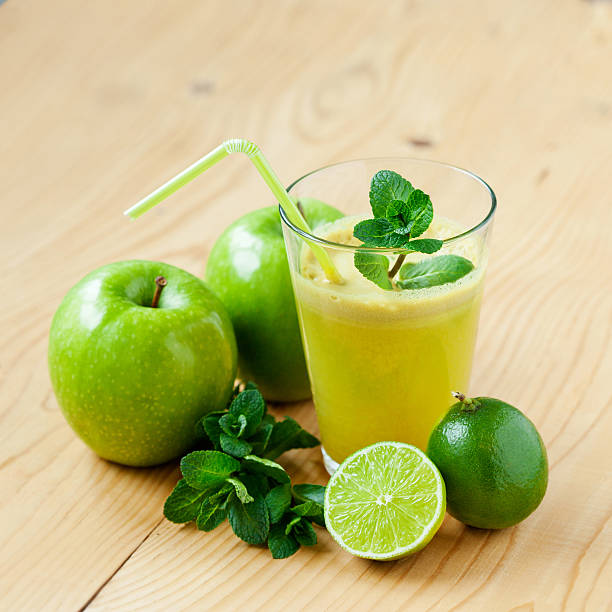 Fresh juice A glass of fresh apple, lime and mint juice, shallow depth of field granny smith apple stock pictures, royalty-free photos & images